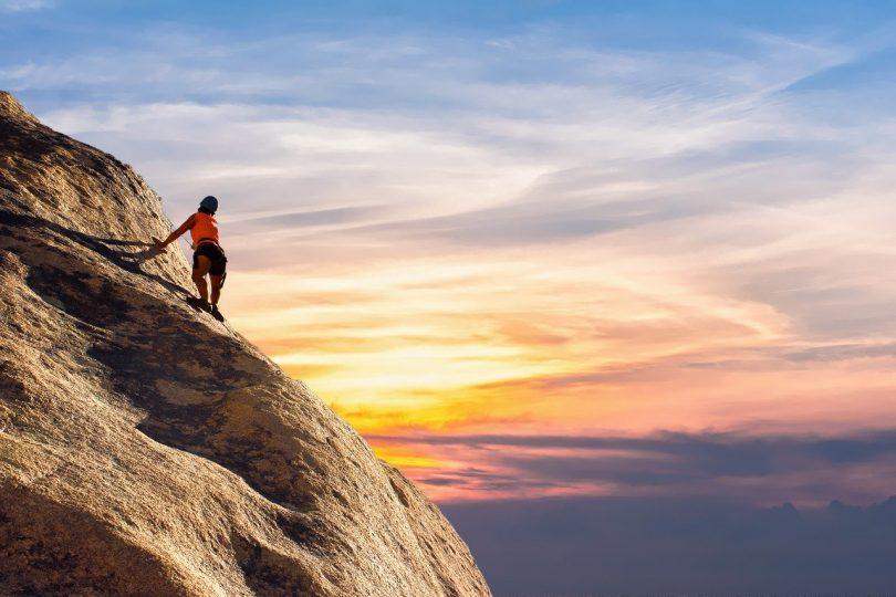 mujer escalando con imagen de puesta de sol