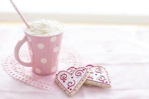 Imagen de una taza y unas galletas en forma de corazón