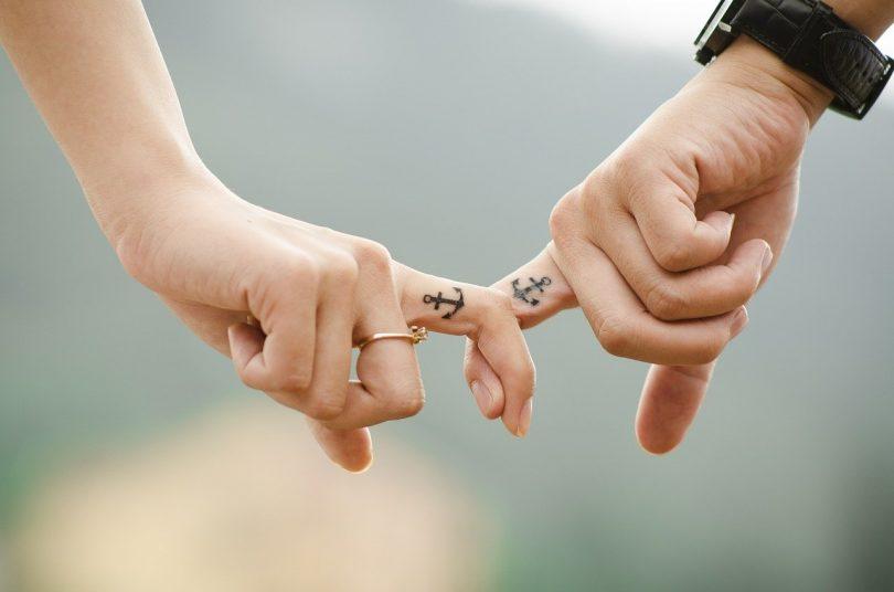 mano de una mujer y hombre con el mismo tatuaje en el dedo índice