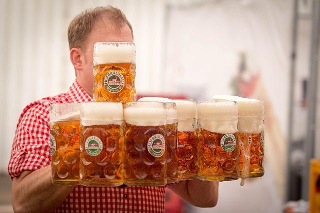 Imagen de un hombre manejando varias jarras de cerveza