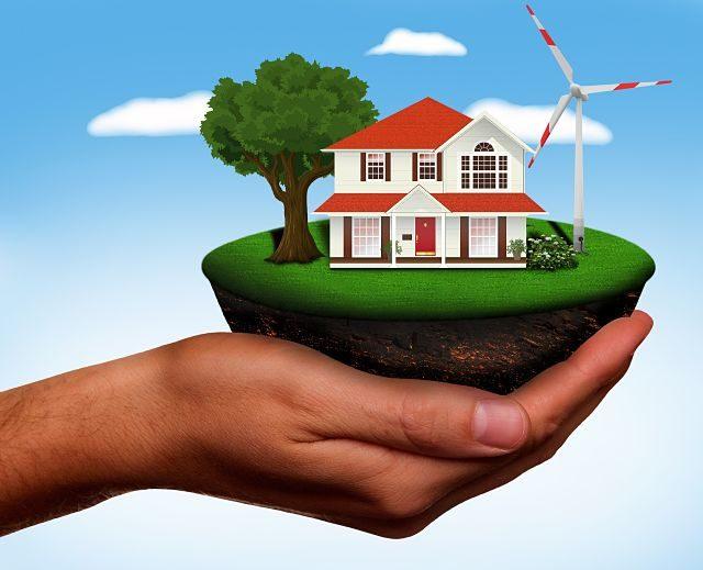 Ilustración de una casa y un molino de viento en una mano