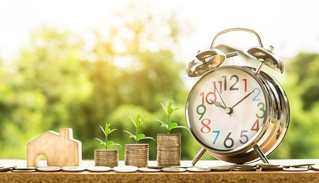 Imagen de unas monedas, una casa de madera y un reloj