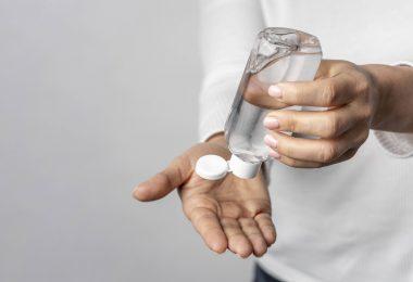 unas manos poniendose gel para manos de un bote transparente