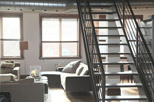 Imagen de un salón con una escalera que conduce al piso de arriba