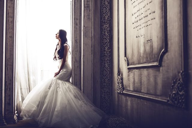 Imagen de una mujer vestida de novia junto a una ventana