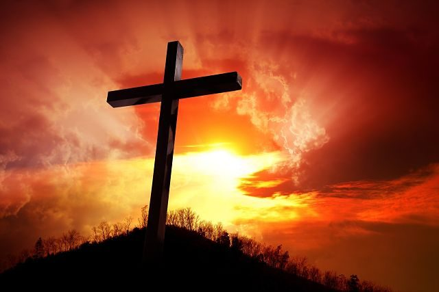 Imagen de una cruz sobre un montículo al amanecer