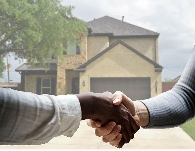 Imagen de dos personas dándose la mano con una casa al fondo