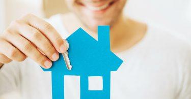 chico sonriendo de fondo aguantando una casa azul de papel y una llave