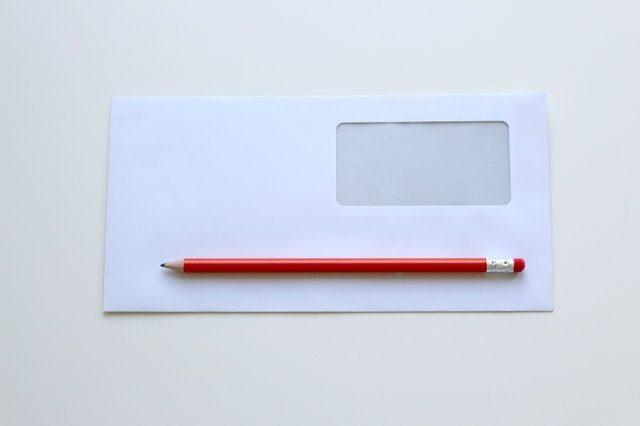 sobre de carta con un lápiz rojo encima