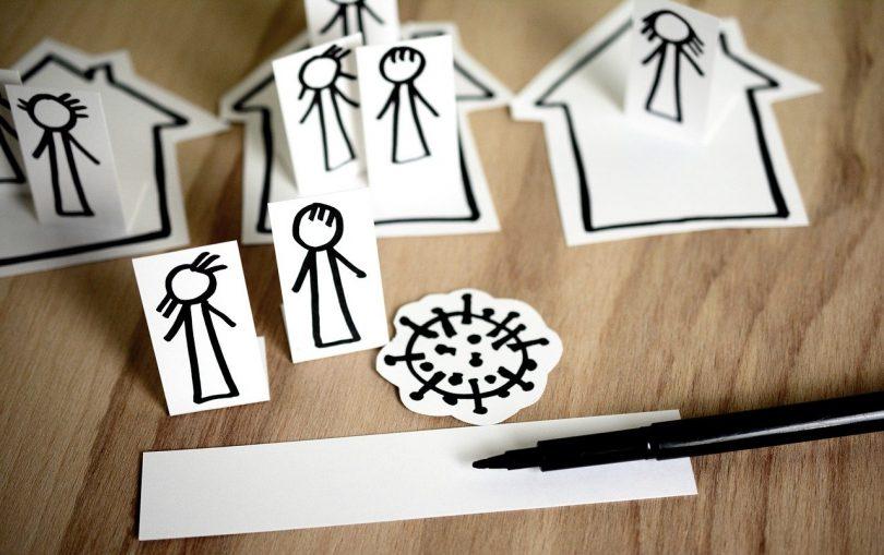 dibujos de personas y casas y un virus sobre una mesa de madera y un rotulador negro