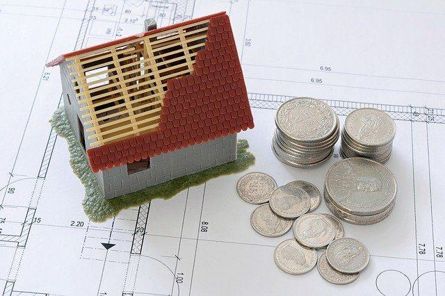 casa de miniatura con el techo a medio construir sobre planos y monedas a un lado