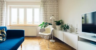 salón moderno con sofá azul y butaca blanca