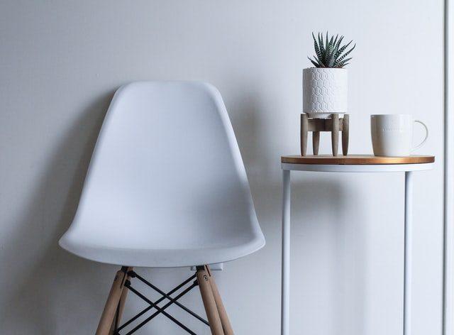 silla blanca junto con mesita con planta y taza