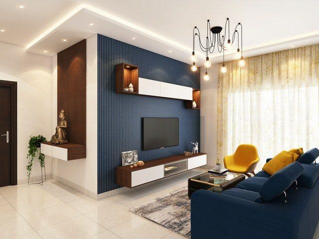 salón con dos paredes pintadas y muebles de tv con sofá y butaca