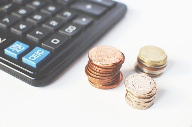 calculadora y monedas sobre un fondo blanco