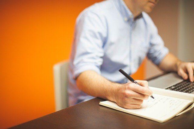 chico escribiendo sobre una libreta con un ordenador portátil al lado en un fondo naranja