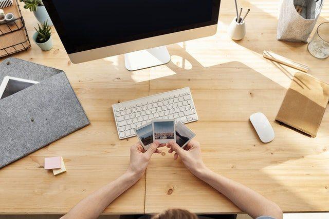persona cogiendo fotos instantáneas delante de la pantalla de un ordenador