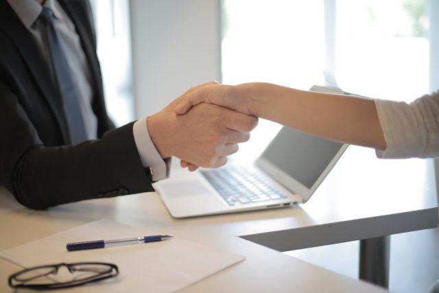 Dos personas encajando la mano con un ordenador de fondo
