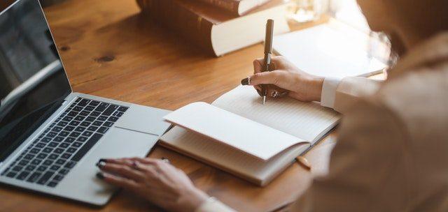 una chica con un ordenador portátil y escribiendo en una libreta