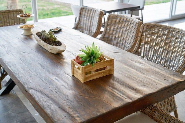 Mesa de madera con centro de mesa de flores y comida