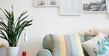 Sofá con cojines de colores juntoa mesita auxiliar verde con planta y lampara y cuadros blancos encima