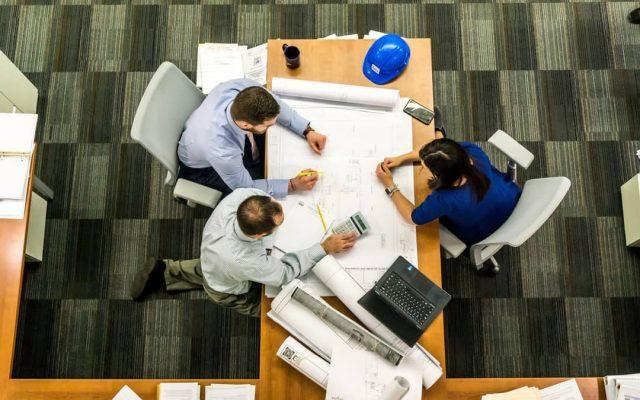 Arquitectos sobre plano firma de contrato de venta piso