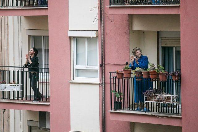 dos mujeres aplaudiendo desde sus balcones