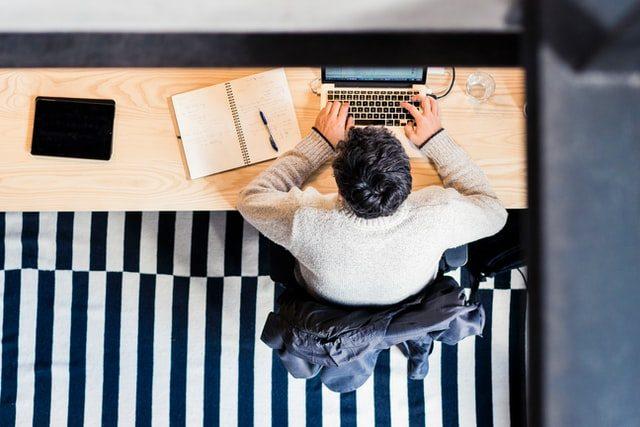 chico frente a un ordenador con una libreta al lado