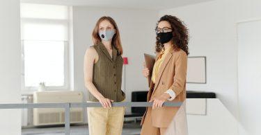 mujeres de negocios con mascarillas en la cara