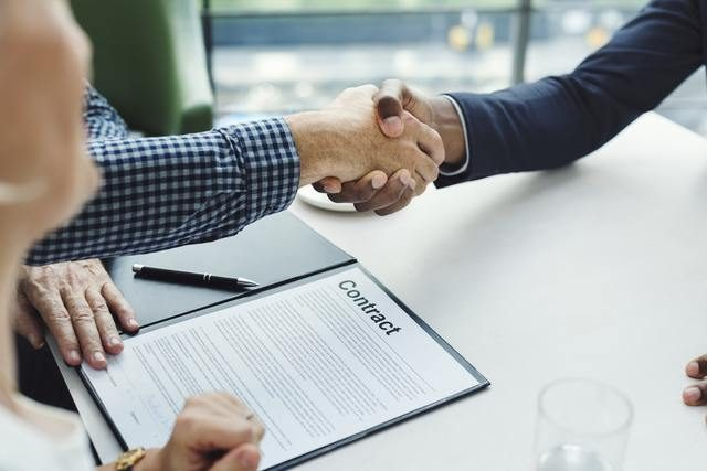 cogida de manos delante de un contrato de alquiler de piso