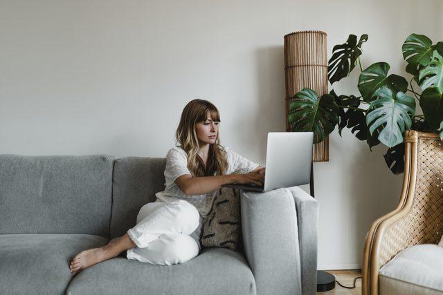 Mujer sentada en el sofá con un ordenador portátil junto a una planta