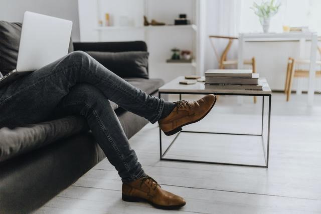 hombre sentado en el sofá con un ordenador