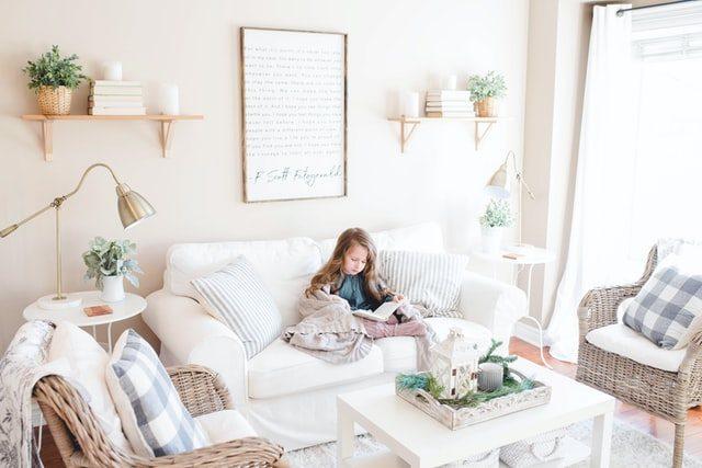 nilña sentada en el sofá de un salón de tonalidades claras