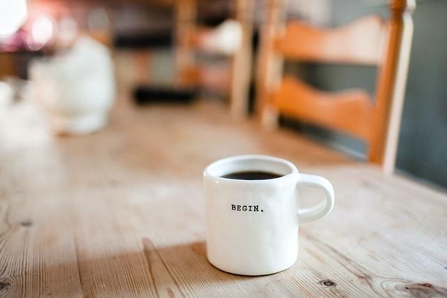 taza blanca con la palabra empezar