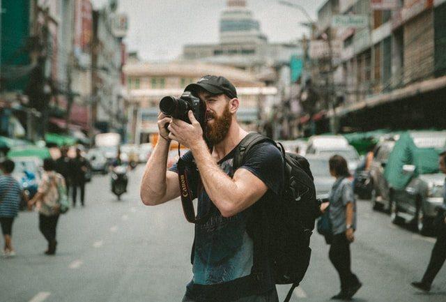chico con barba haciendo fotos en la calle con una cámara reflex