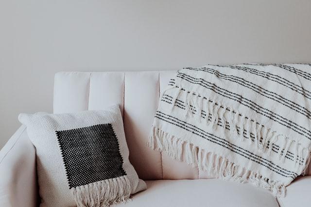 cojín blanco y negro sobre sofá blanco junto a una manta rallada