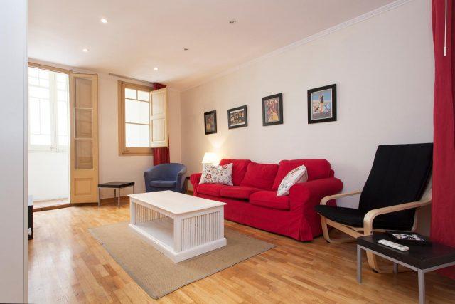 Salón de piso bonito con suelo de madera y sofá rojo