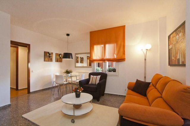 Salón con sofás naranjas. Piso bonito Barcelona