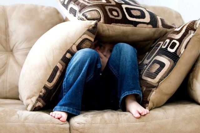 niño escondido en el sofá que no quiere ver maratón de series