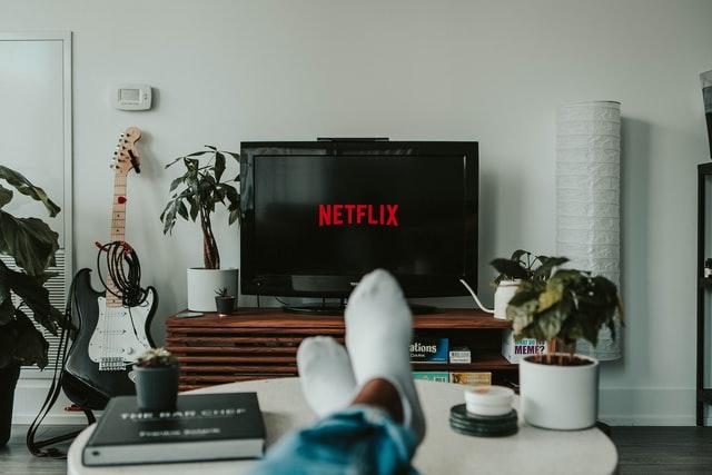 Pessoa sentada no sofá vendo televisão