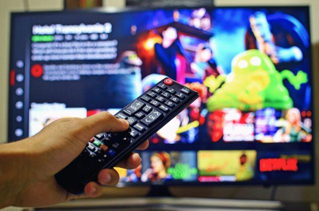 mando y televisión con Netflix, todo listo para ver una maratón de series