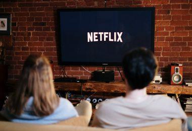 pareja en el sofá de su casa con Netflix en la televisión preprarados para hacer una maratón de series