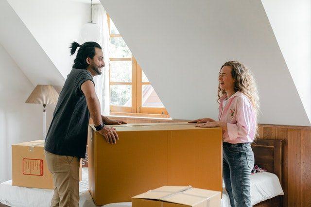 Casal abrindo as caixas de mudança em seu novo apartamento